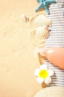 Tube de crème solaire, étoiles de mer, plumeria frangipanier et coquillages sur le sable