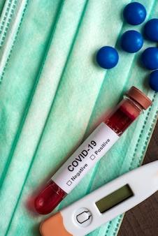 Tube à essai contenant un échantillon de sang pour tester la présence de coronavirus / covid-19 avec masque, comprimé de médicament et thermomètre.
