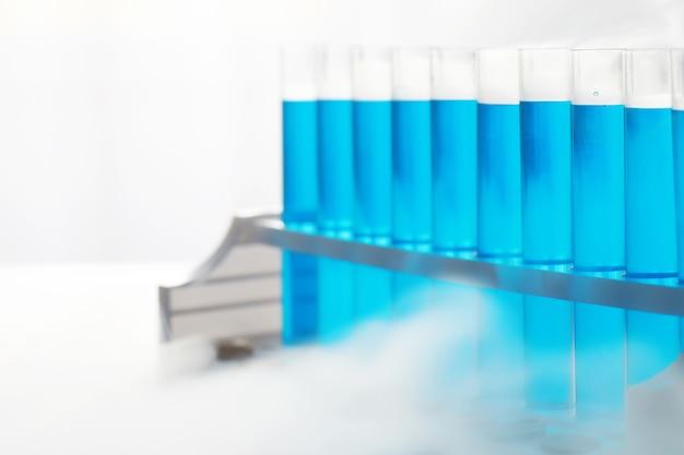 Le tube à essai de verre déborde de la nouvelle solution liquide de bleu de potassium effectue une analyse de réaction prend différentes versions de réactifs à l'aide de produits chimiques pharmaceutiques contre le cancer .