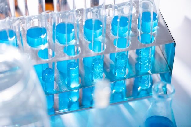 Un tube à essai en verre déborde d'une nouvelle solution liquide de bleu de potassium effectue une réaction d'analyse prenant différentes versions de réactifs à l'aide de la fabrication de médicaments pharmaceutiques du cancer