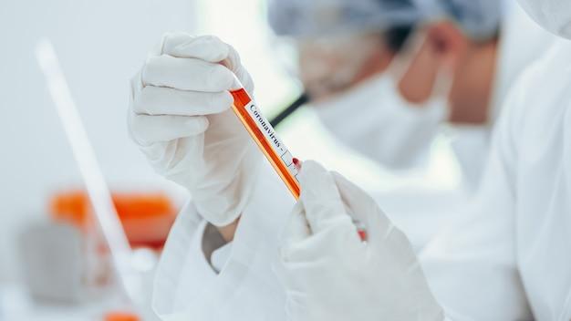 Tube étiqueté avec un test de coronavirus entre les mains d'un assistant de laboratoire