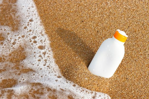 Tube avec protection solaire spf sur la plage de sable fin