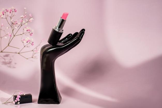 Tube unique de rouge à lèvres rose sur fond rose avec des fleurs