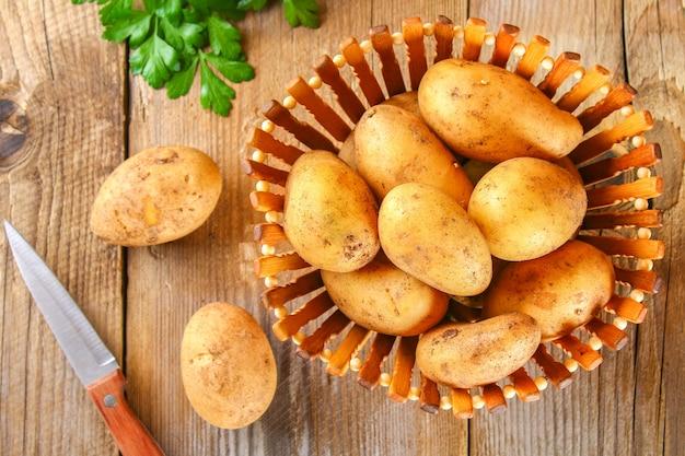 Tubercules de pommes de terre jaunes sur une vieille table en bois.