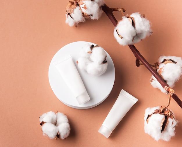 Tubes blancs de crème et branche décorative avec des fleurs de coton