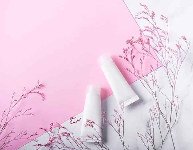 Tubes blancs de crème et branche décorative