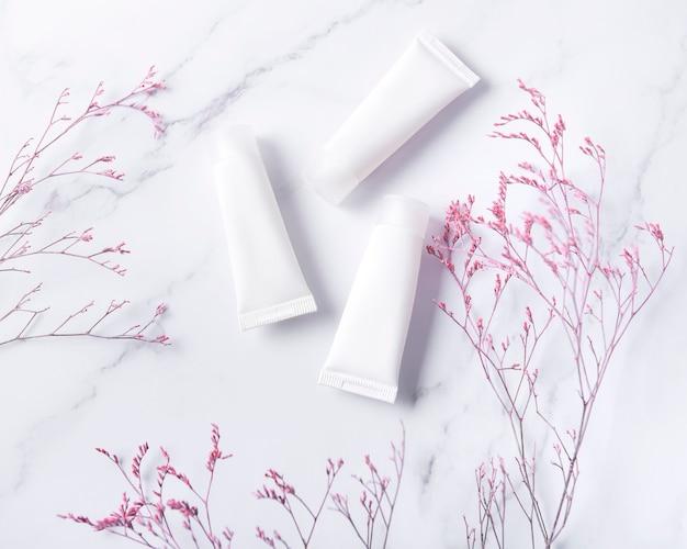 Tubes blancs de crème sur fond de marbre et branche décorative