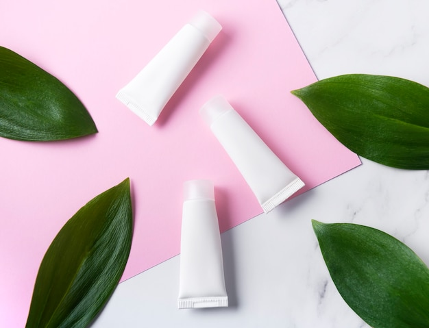 Tubes blancs de crème sur fond de marbre et rose à feuilles vertes