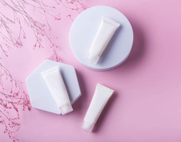 Tubes blancs de crème sur fond rose et branche décorative