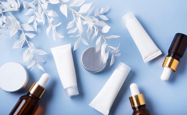 Tubes blancs de crème et d'huiles essentielles sur un tableau bleu