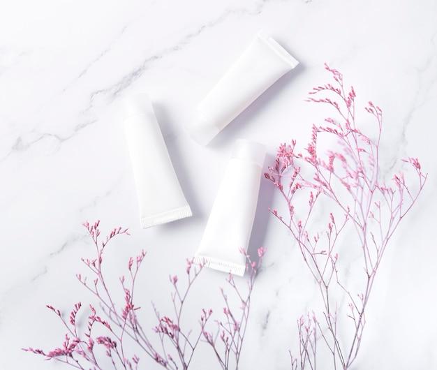 Tubes blancs de crème sur une table en marbre et branche décorative
