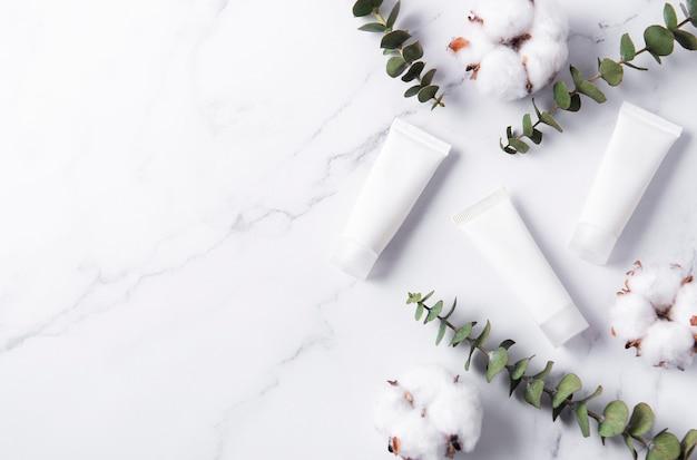 Tubes blancs de crème sur une table en marbre avec des fleurs d'eucalyptus et de coton