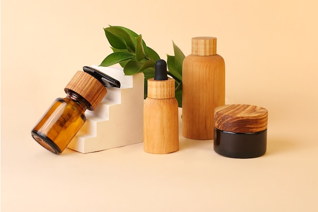 Tubes et bouteilles écologiques en bois naturel et verre brun près du piédestal géométrique. feuilles naturelles fraîches en arrière-plan. concept de cosmétique biologique zéro déchet.