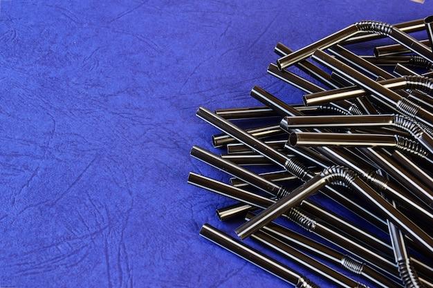 Les tubes à cocktail sont empilés à droite sur une surface bleue décorative.