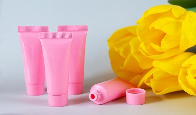 Tubes cosmétiques rose en plastique à côté de fleurs de tulipes jaunes close-up