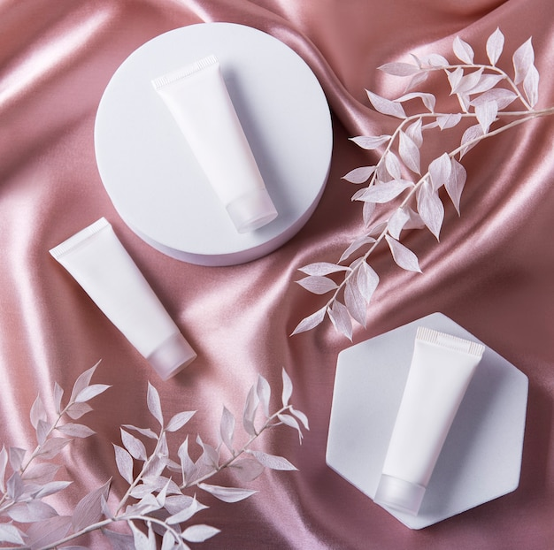 Tubes de crème blanche sur soie marron clair et feuilles blanches