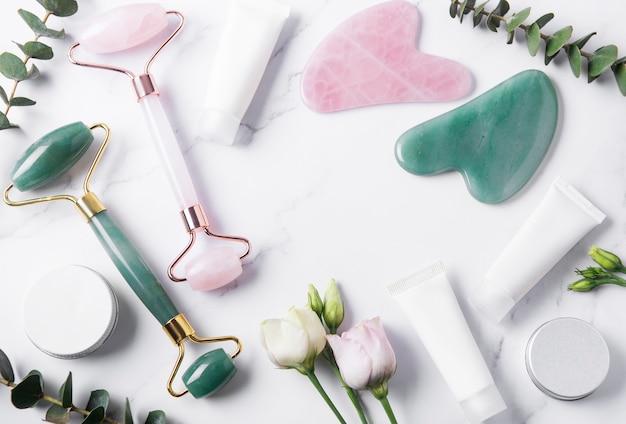 Tubes de crème de produits cosmétiques, rouleau de visage et eucalyptus sur table en marbre. vue de dessus. spa relax, soin du corps, spa, concept de soins de la peau.