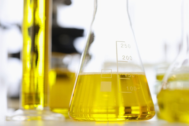 Tubes à essai et flacons avec liquide jaune debout sur la table de gros plan de laboratoire chimique