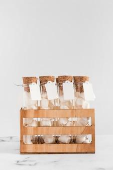 Tubes à essai guimauve avec étiquette dans une caisse sur fond blanc