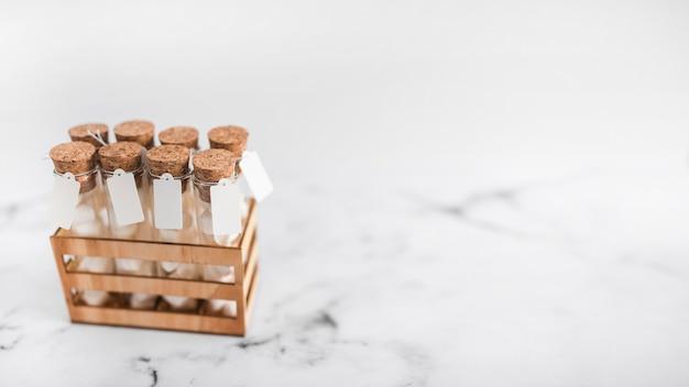 Tubes à essai guimauve avec étiquette dans une caisse sur fond de marbre