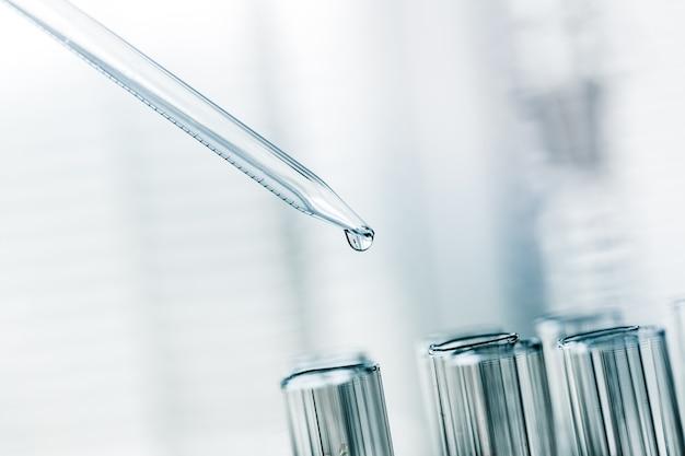Tubes à essai de laboratoire scientifique et pipette avec goutte, gros plan d'équipement de laboratoire