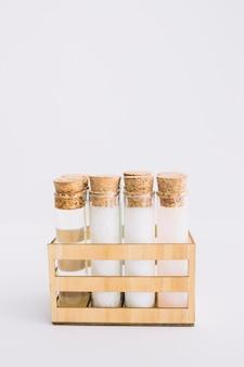 Tubes à essai de produits de spa bio disposés dans un récipient en bois sur une surface blanche
