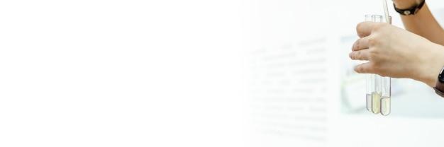 Tubes à essai en verre dans ses mains et tubes à essai avec des échantillons de sang pour des tests médicaux dans un stand de laboratoire blanc comme neige. l'expert médico-légal tient un tube à essai avec un échantillon d'adn. un test de paternité. bannière.
