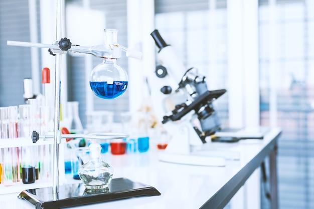 Tubes à essai avec verrerie de laboratoire sur la table en arrière-plan de laboratoire, recherche et concept scientifique