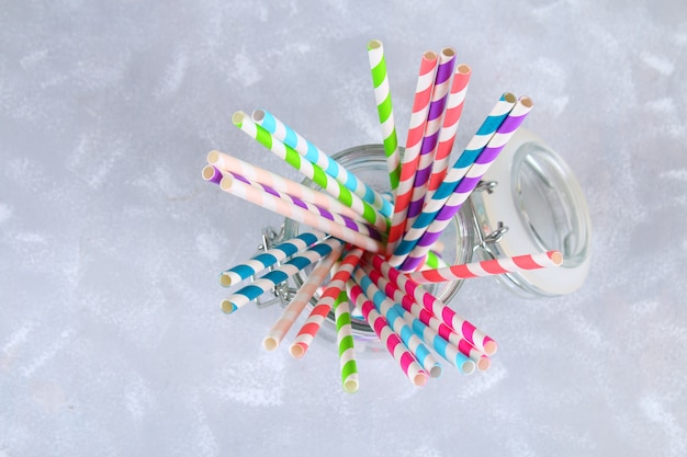 Tubes jetables en papier à rayures colorées dans un bocal sur fond gris