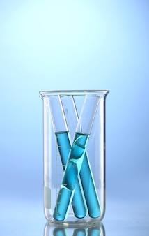Tubes de laboratoire avec liquide bleu dans un bécher de mesure avec réflexion sur bleu