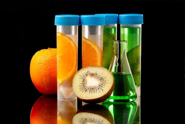 Tubes lb remplis de liquide ou de parties de fruits sur fond noir.