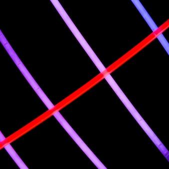 Tubes rouges au néon sur des néons violets sur fond sombre