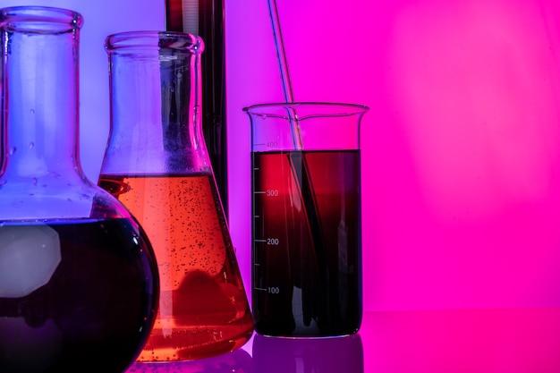 Tubes en verre de laboratoire avec des produits chimiques sur fond rose vif