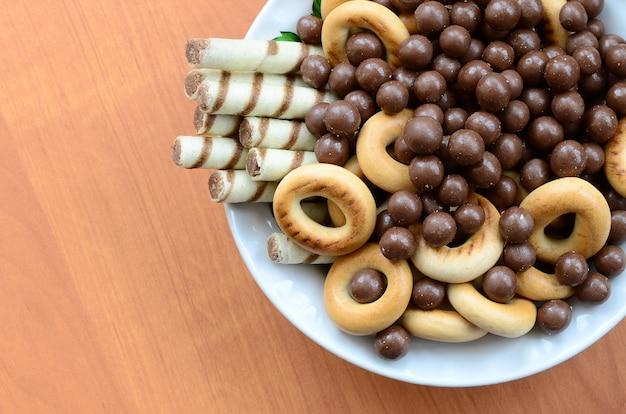 Des tubules croustillants, des boules de chocolat fondant et des bagels reposent dans une assiette blanche sur une table en bois.
