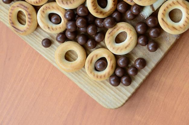 Des tubules croustillants, des boules de chocolat fondant et des bagels reposent sur une surface en bois.