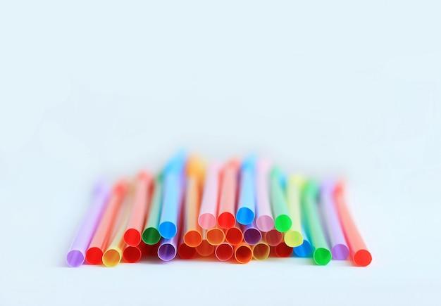 Tubules en plastique multicolores brillants sur un fond blanc,.