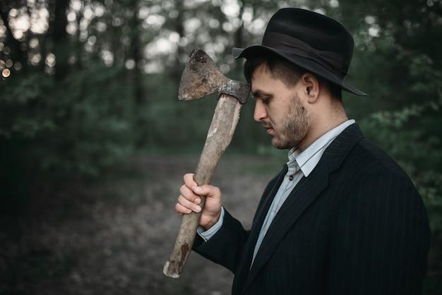 Tueur en série avec une hache dans la forêt de nuit