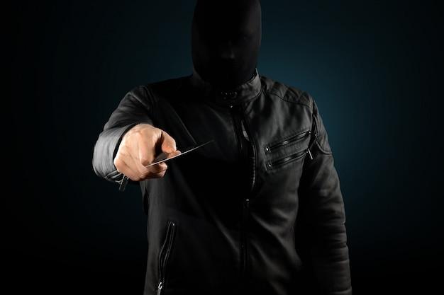 Le tueur en série, un maniaque avec un couteau et un chuolkom noir sur la tête