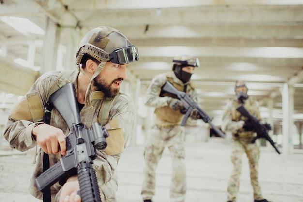 Un tueur sérieux et fort se tient avec deux autres soldats dans une longue pièce
