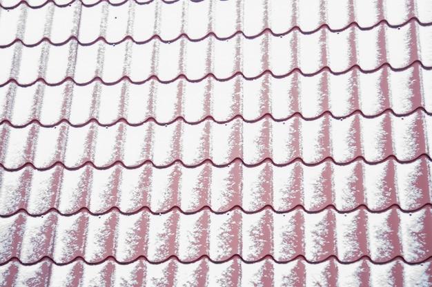 Tuile de toit en métal rouge gros plan de texture recouverte d'une fine couche de flou de neige