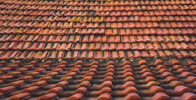 Tuiles de toit vintage moisies rouges dans les rayons du soleil levant.