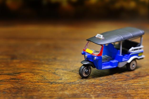 Tuk tuk taxi jouet sur table en bois
