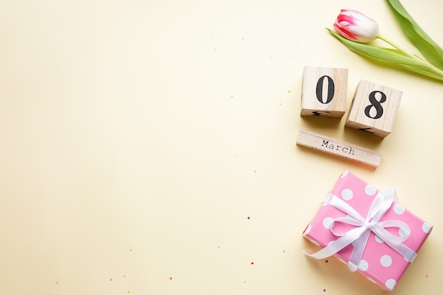 Tulipe avec un cadeau et un calendrier en bois sur fond beige, pose à plat. 8 mars. journée internationale de la femme.