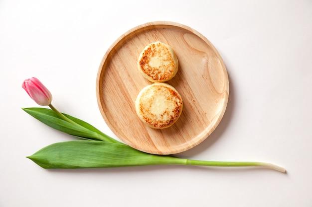 Tulipe rose frais de fleur fraîche sur la plaque ronde en bois, deux gâteaux au fromage frits d'or.