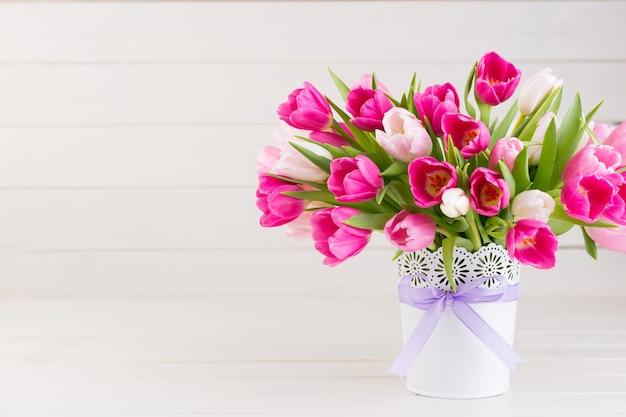 Tulipe rose sur la surface blanche. carte de voeux de pâques et de printemps.