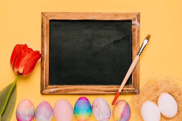 Tulipe rouge près des oeufs de pâques avec tableau noir et pinceau sur fond jaune