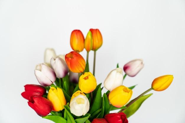 Tulipes artificielles multicolores sur fond blanc. décorer l'intérieur de la maison avec des plantes. fleuriste. vente de fleurs, plantes et compositions de celles-ci.