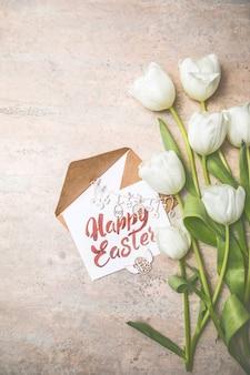 Tulipes blanches, cartes de joyeuses pâques sur fond gris. vue de dessus à plat