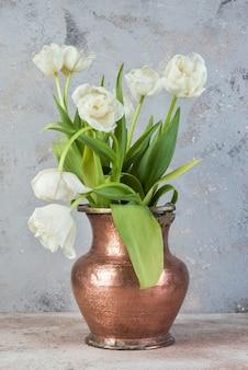 Tulipes blanches dans un vase en cuivre ancien