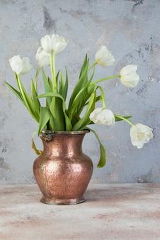 Tulipes blanches dans un vieux vase en cuivre